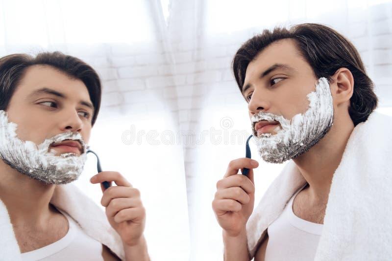 Bearded man neatly shaves beard in shaving foam. Bearded men neatly shaves beard in shaving foam. Morning bath procedures royalty free stock image