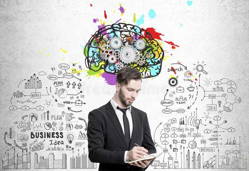 Bearded man with notebook and brain cogs. Portrait of a serious young businessman writing in his notebook standing near a concrete wall with a colorful brain stock photo