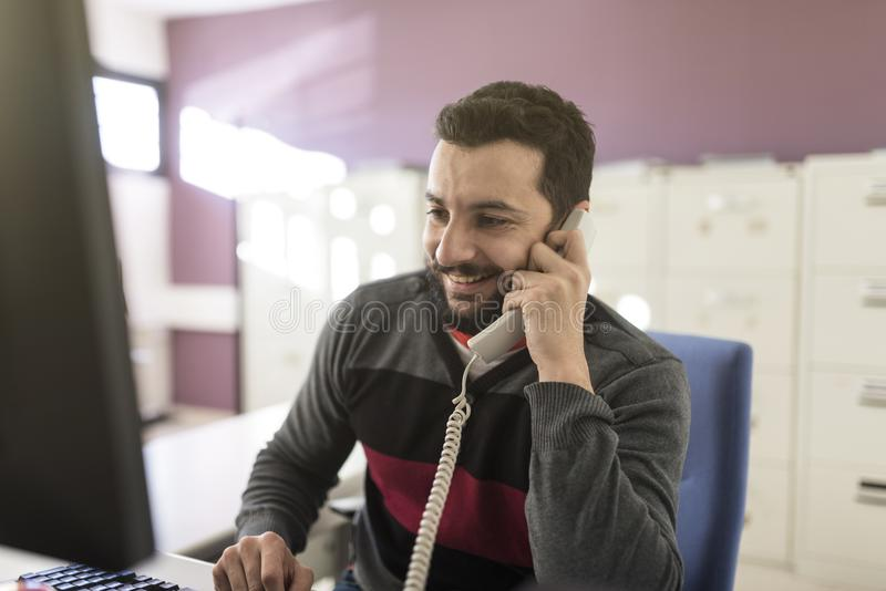 Bearded man in office at phone with ambient light talking. Bearded man in office at phone with ambient light working on line with customers royalty free stock photos