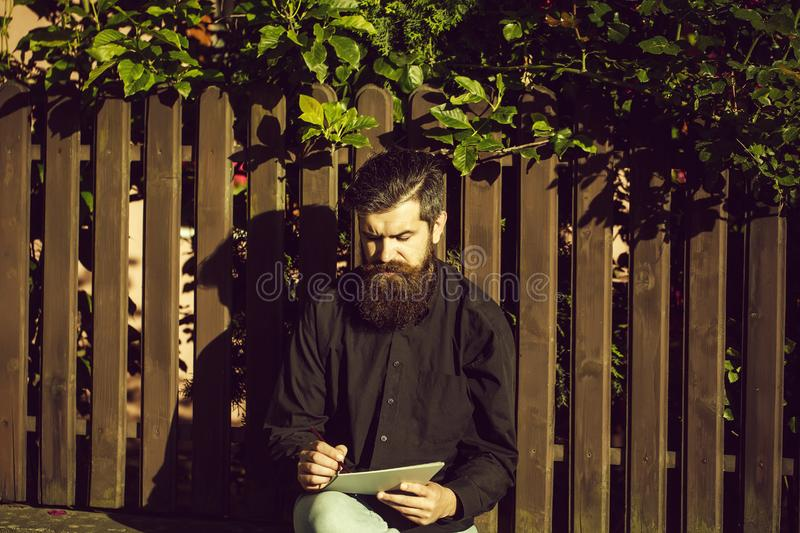 Bearded man outdoor with pencil and note stock images