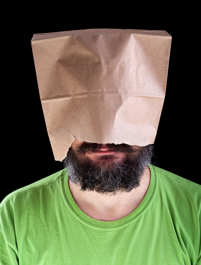 Bearded man with paper bag on his head smiling. Bearded man with paper bag on his head wearing a smile - ignorance is bliss concept stock images