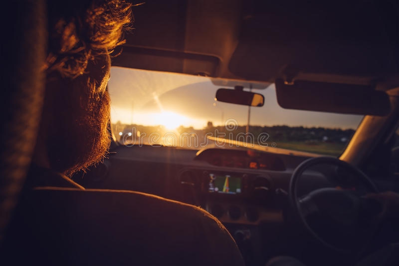 Bearded Man passenger in a Car looking on sunset road royalty free stock image