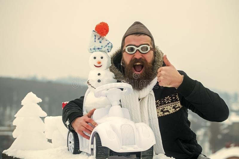 Bearded man in pilot hat and glasses showing thumbs up. Excited hipster on winter landscape. Snowman driving toy car on white sky. Christmas and new year royalty free stock photos
