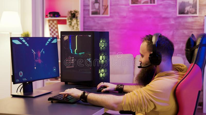 Bearded man playing online video games on his pc royalty free stock photo