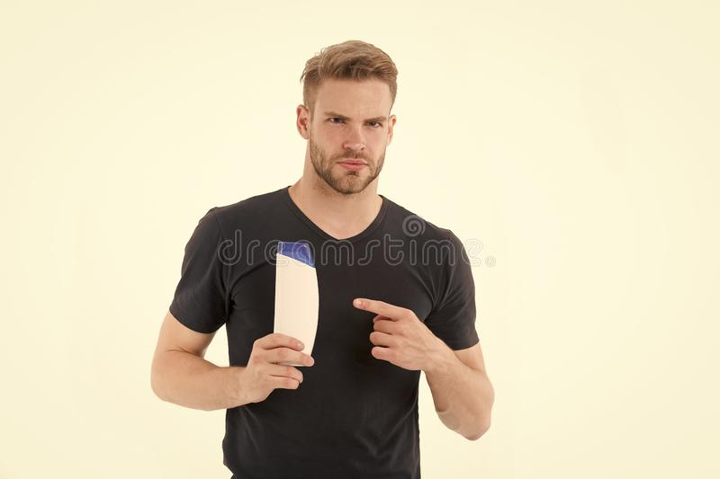 Bearded man point finger at shampoo or gel bottle. Macho with beard in tshirt show cosmetic for bath or shower. Presenting product concept. Hair care and beard royalty free stock photography