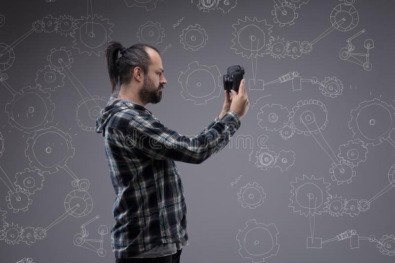 Bearded man with a pony tail taking a selfie. Holding up a digital camera in front of his face in profile view against a chalkboard with hand drawn cogs for stock photos