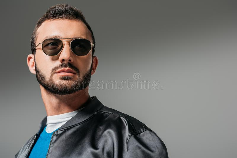 Bearded man posing in black bomber and sunglasses. Isolated on grey royalty free stock image