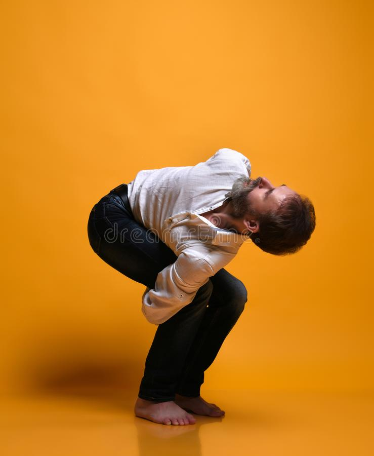 Old man practicing yoga doing stretching exercises against yellow background royalty free stock images