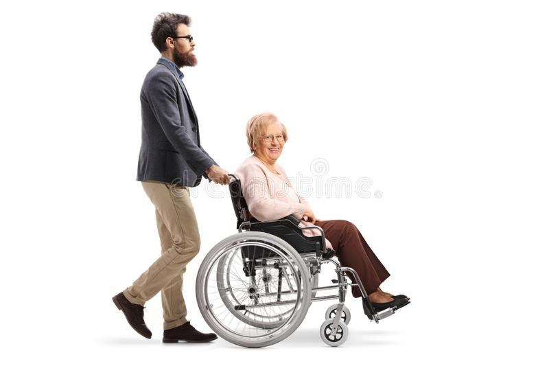 Bearded man pushing a senior woman in a wheelchair stock photo