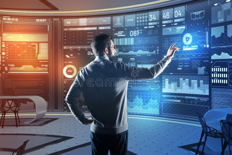 Bearded man putting his hand up while pointing to the transparent screen. Noticing changes. Calm clever experienced programmer standing in his equipped modern stock photos