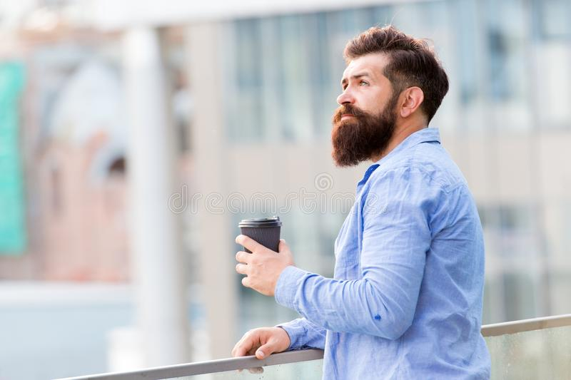 Bearded man relax. brutal hipster with coffee cup. energy charge. Male barber care. copy space. Time zone. thoughtful. Man drink take away coffee outdoor stock photo