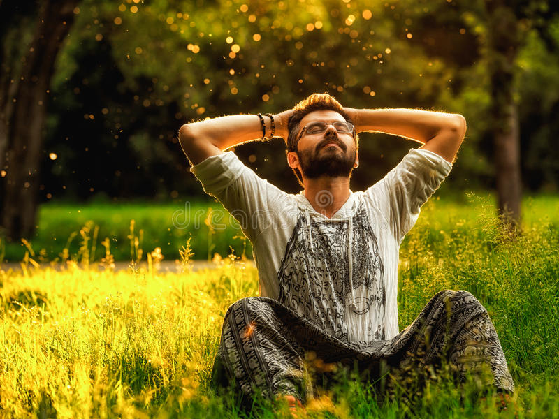 A bearded man is relaxing on green grass in the park stock photos
