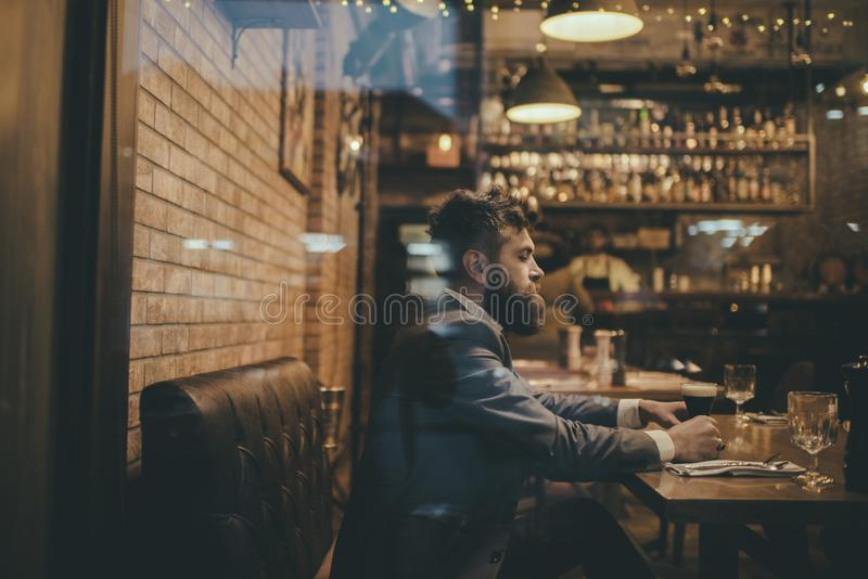 Bearded man rest in restaurant with beer glass. serious bar customer sit in cafe drinking ale. Date meeting of hipster royalty free stock photos