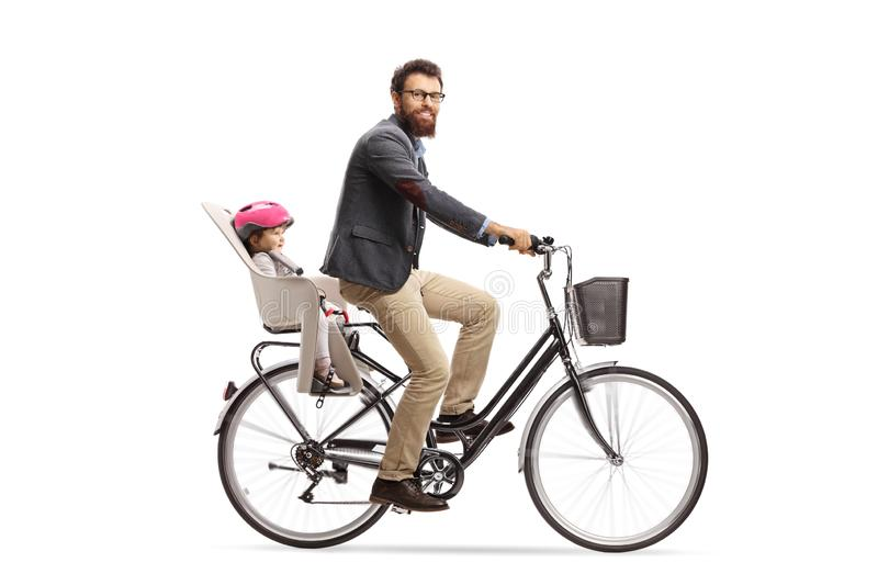 Bearded man riding a little child on a bicycle and looking at the camera royalty free stock images