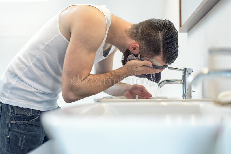 Bearded man rinsing his face in the bathroom royalty free stock photo