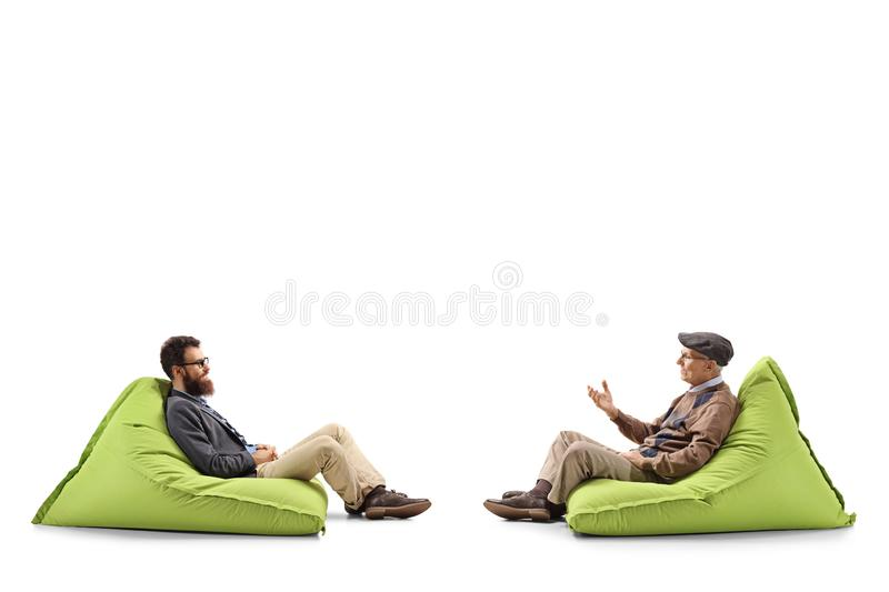 Bearded man and a senior man sitting on bean bags and having a conversation stock photos