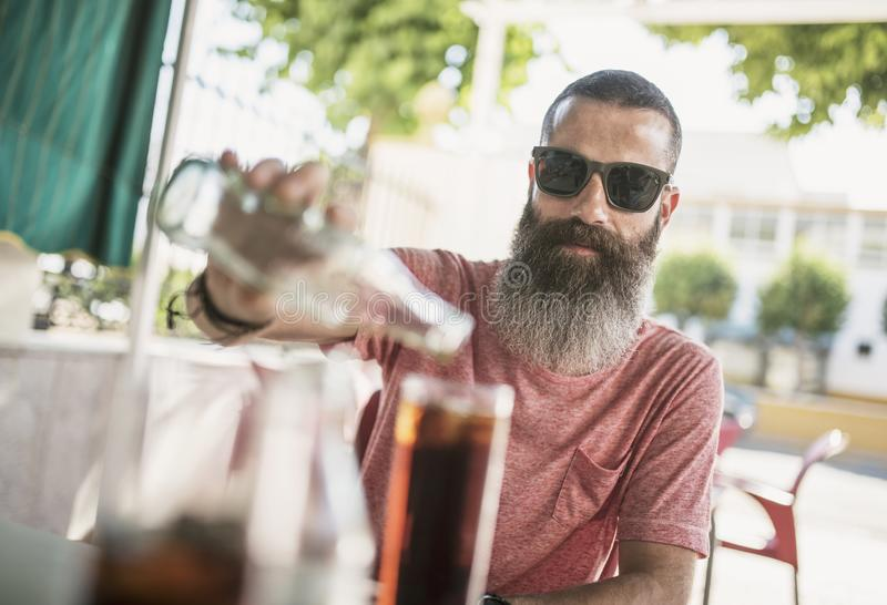 Bearded man serving coke soda on whishky drink in outdoors bar terrace stock image
