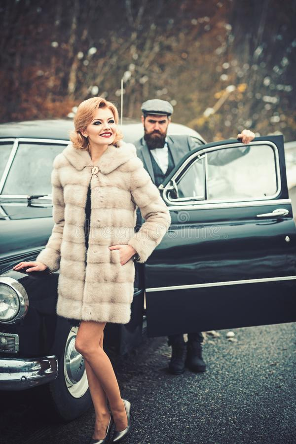 Bearded man and sexy woman in fur coat. Escort of girl by security. Retro collection car and auto repair by mechanic stock photography