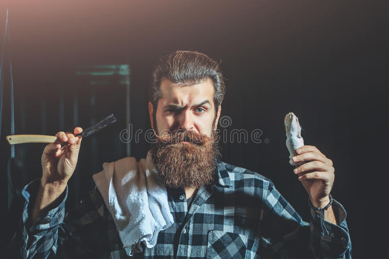 Bearded man shaves with razor stock photo