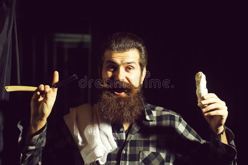 Bearded man shaves with razor royalty free stock photo
