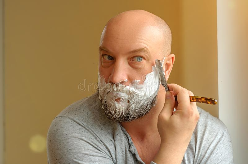 A bearded man shaves with a straight razor stock photography