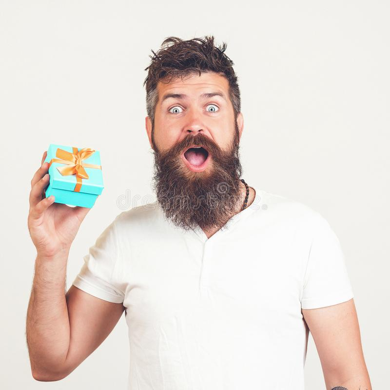 Bearded man with shocked facial expression. Man shows gift box. Hipster surprised by best present ever. Sale concept. Brutal royalty free stock photography