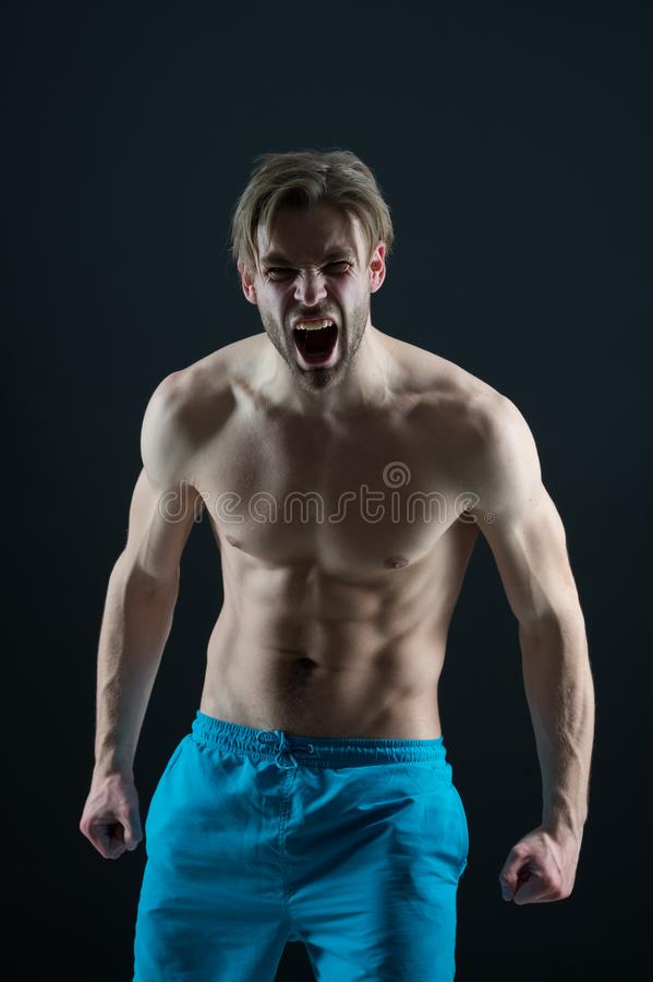 Bearded man shout with anger, health. Angry macho with fit bare torso, chest and belly, fitness. Athlete guy with six pack, ab, tr. Iceps and biceps muscles royalty free stock image