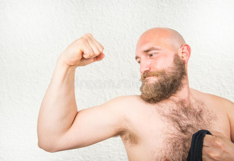 a bearded man showing his arms muscle stock photography