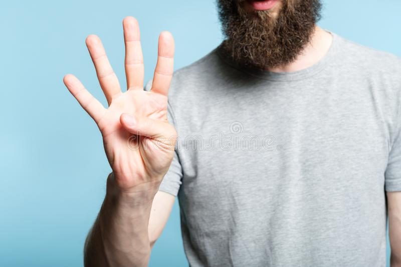 Bearded man show hand number four counting gesture royalty free stock photos