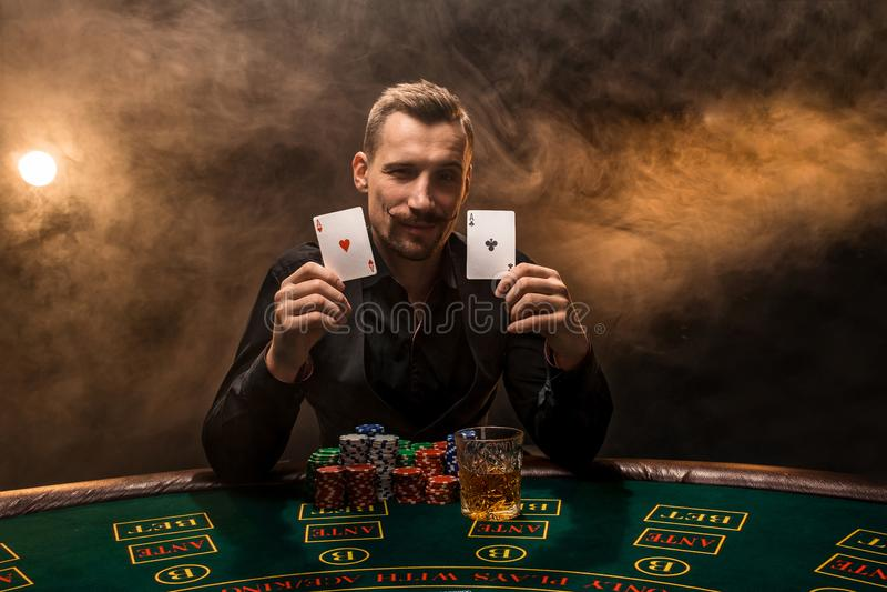 Bearded man showing poker cards on smoke black background royalty free stock photography