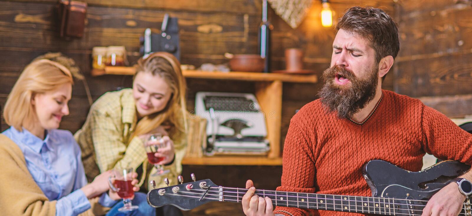 Bearded man singing heart-warming love song. Man with hipster beard playing moving melody on guitar. Musician royalty free stock images
