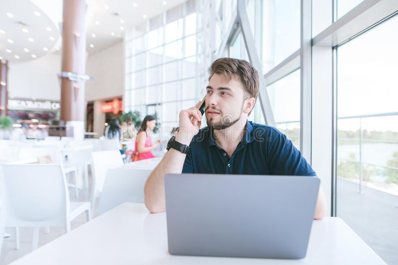 Bearded man sits in a light cafe, works on a laptop and talks over the phone. Portrait of a freelancer using a laptop in a modern design cafe stock image