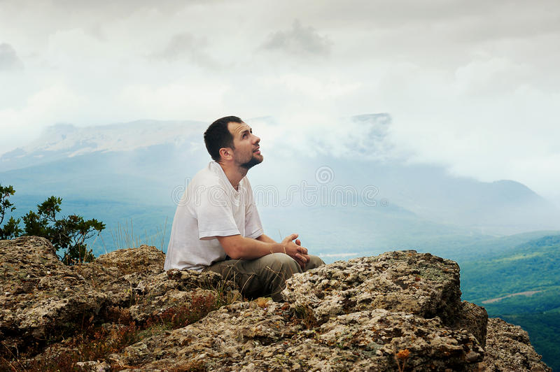 Bearded man sits on top of mountain royalty free stock photography
