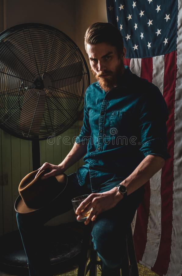 Bearded Man sitting in dark room with American Flag stock image