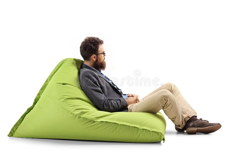 Bearded man sitting on a modern green bean bag chair. Full length profile shot of a bearded man sitting on a bean bag and looking away isolated on white royalty free stock images