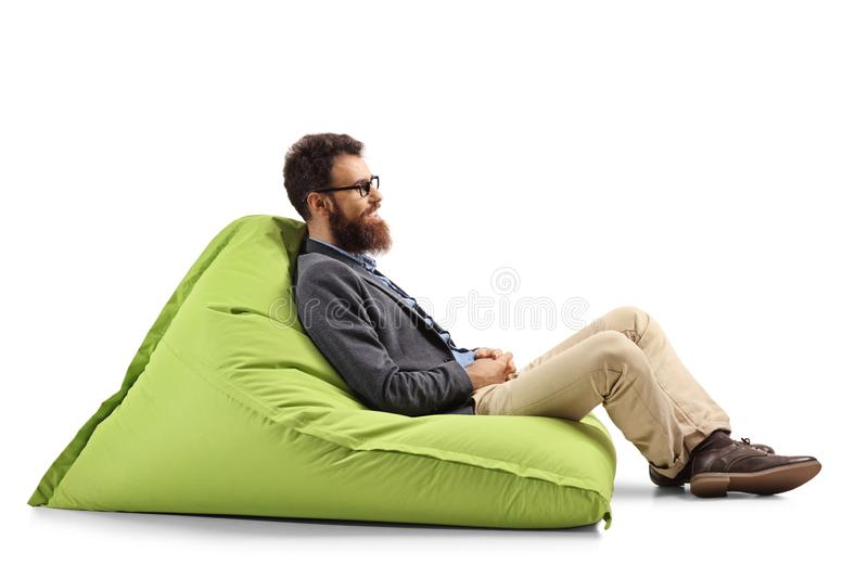 Bearded man sitting on a modern green bean bag chair. Full length profile shot of a bearded man sitting on a modern green bean bag chair isolated on white royalty free stock photography