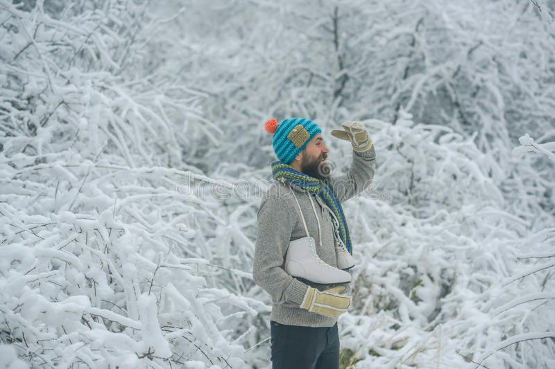Bearded man with skates in snowy forest. stock photos