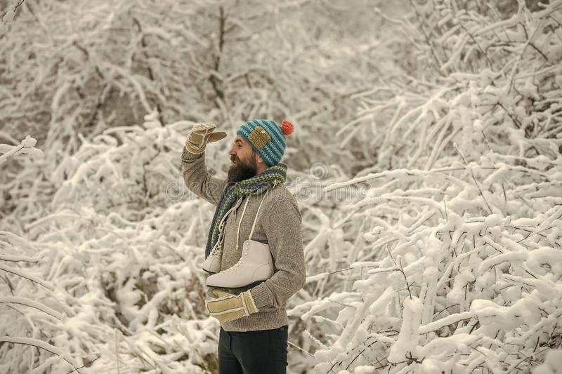 Bearded man with skates in snowy forest. royalty free stock photos