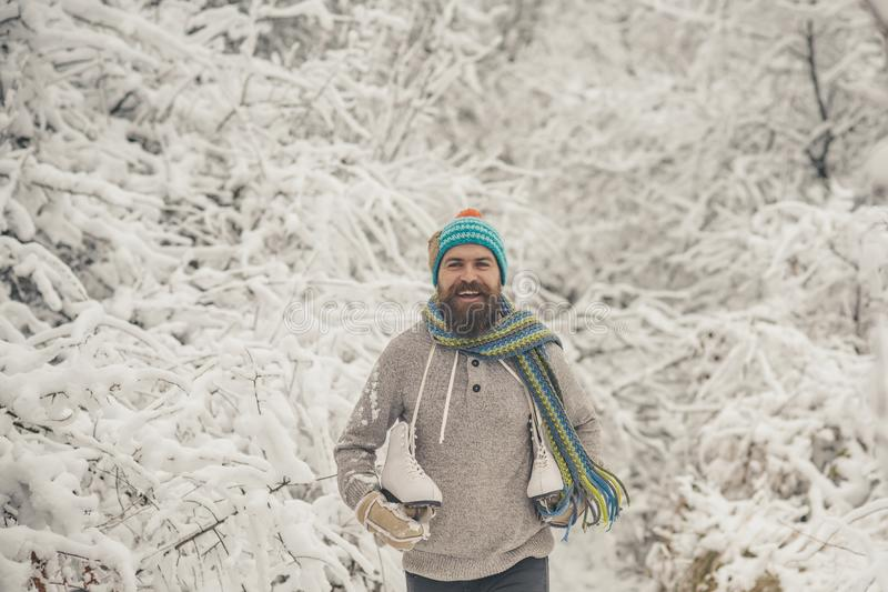 Bearded man with skates in snowy forest. royalty free stock images