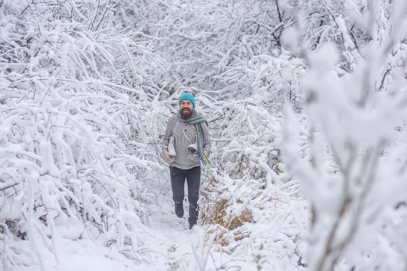 Bearded man with skates in snowy forest. stock photography