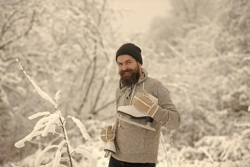 Bearded man with skates in snowy forest. stock image