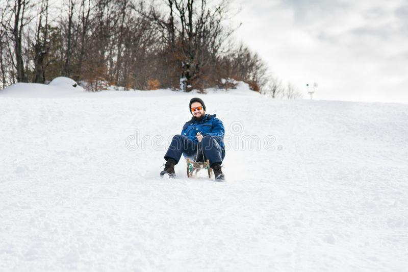 Bearded man sleighing down hill. On the snow royalty free stock photos