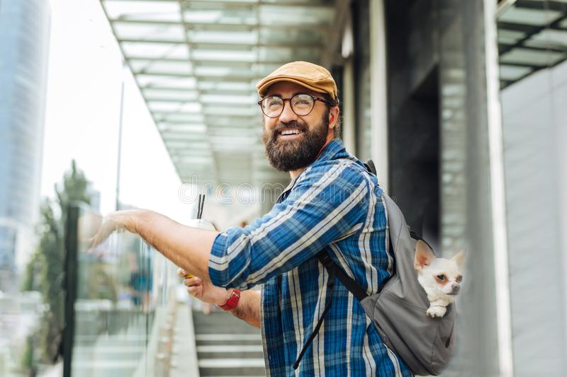 Bearded man smiling while seeing his wife coming to him. Seeing wife. Bearded man wearing glasses and hat smiling while seeing his wife coming to him royalty free stock photo