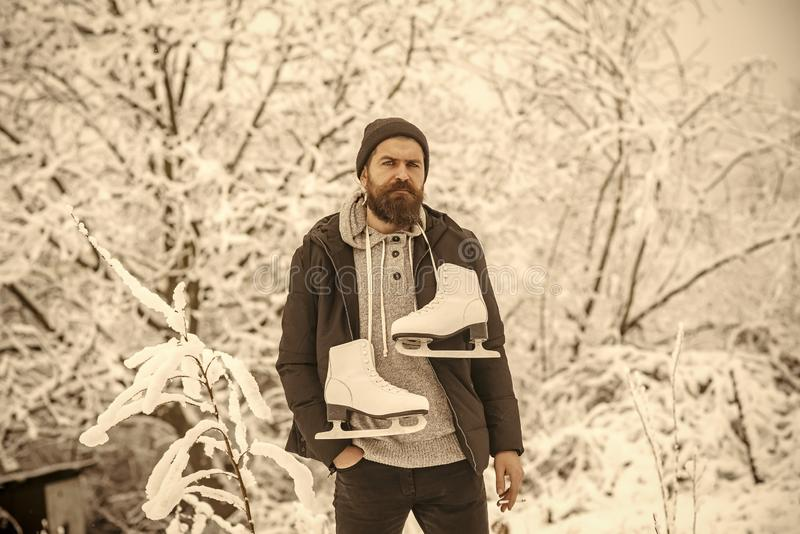 Bearded man smoking cigarette with skates in snowy forest. royalty free stock photos