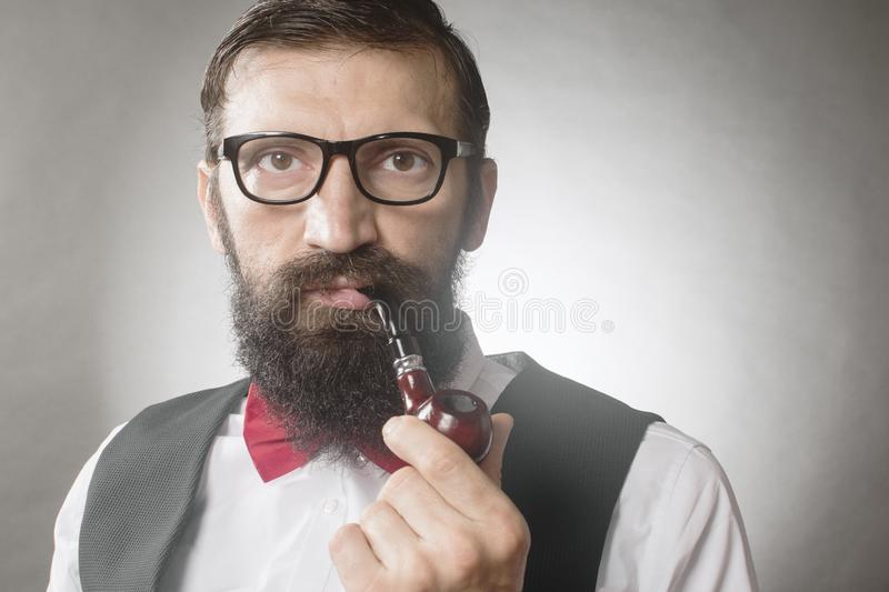 Bearded man smoking pipe vintage portrait. Front view portrait of bearded elegant middle aged man with eyeglasses who is smoking tobacco pipe on gray background royalty free stock photography