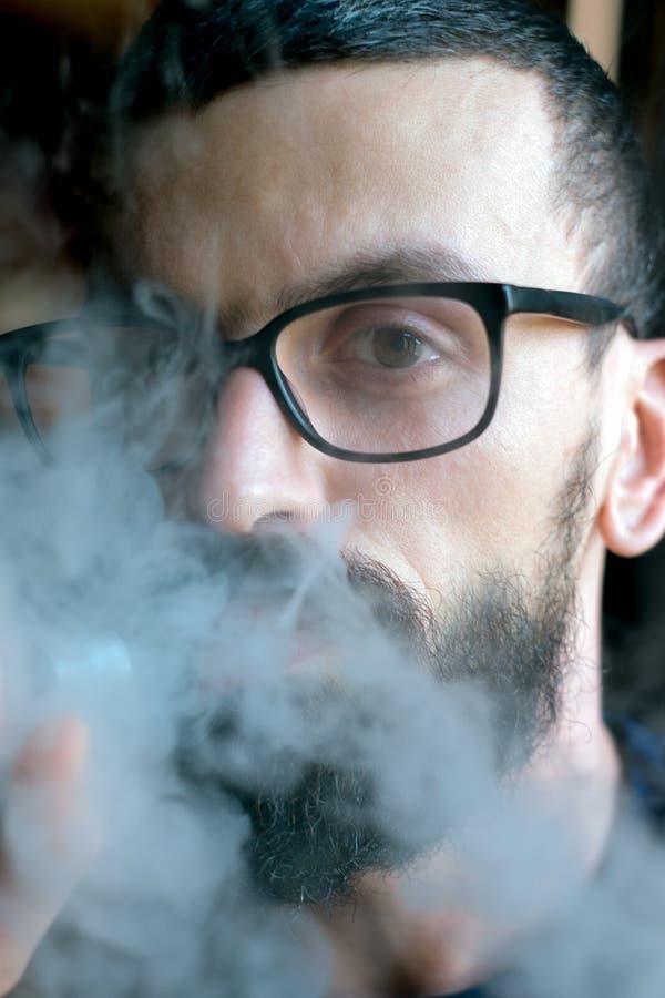 Bearded man smoking vaporizer and blows smoke stock photo