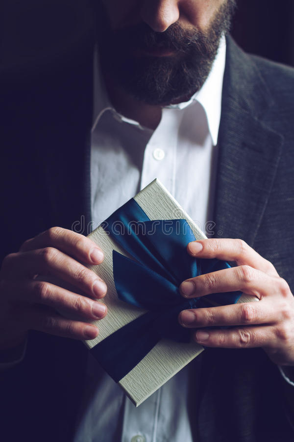 Bearded man in suit opening a gift with blue ribbon. Horizontal close up of Caucasian man with beard in black suit and white shirt holding a gift box with blue stock photo