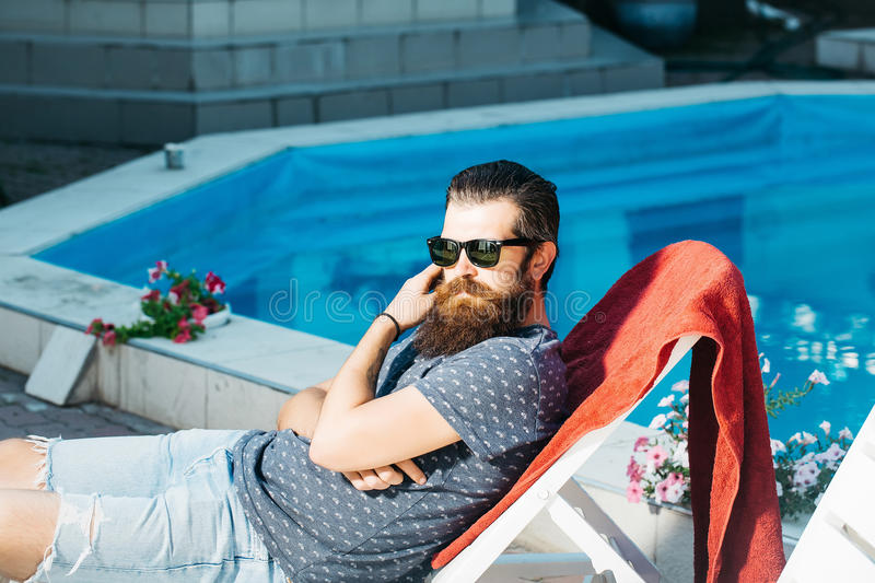 Bearded man in sun glasses at swimming pool. Young handsome bearded man with long beard in sun glasses on face laying on beach chair at swimming pool with blue stock photo