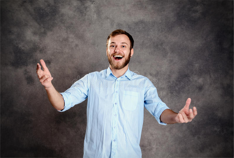 Bearded man is surprised and showing open hands. Young bearded man is surprised and showing open hands royalty free stock photo