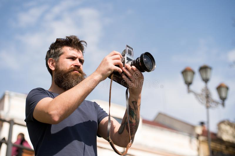 Bearded man taking photo on sunny day. Man with beard and mustache on concentrated face, sky on background, defocused stock photos